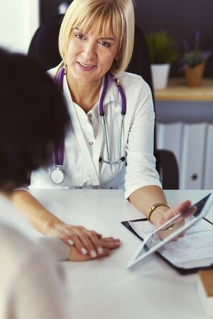 doctor explaining diagnosis to her female patient Фото со стока