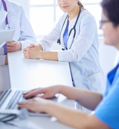 Serious medical team using a laptop in a bright office