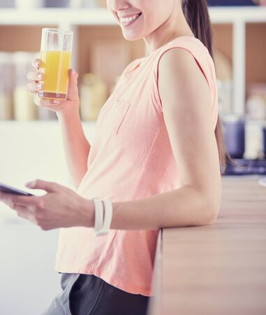 Smiling pretty woman looking at mobile phone and holding glass of orange juice while having breakfast in a kitchen.