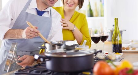 Attractive couple in love cooking and opens the wine in the kitchen while they cook dinner for a romantic evening.