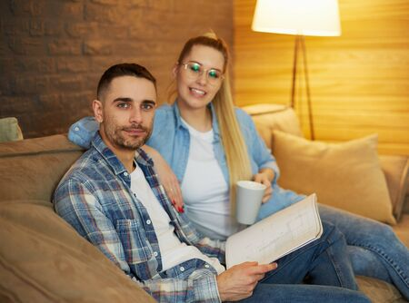 Smiling wife and husband sitting in living room and discussing apartment interior, moving to new home 스톡 콘텐츠