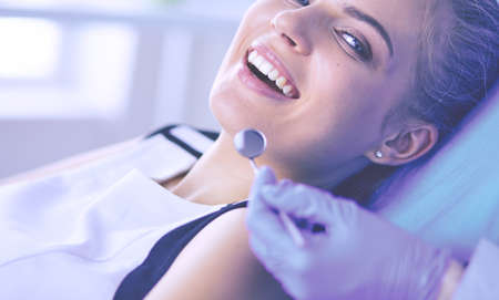 Young Female patient with open mouth examining dental inspection at dentist office. Standard-Bild