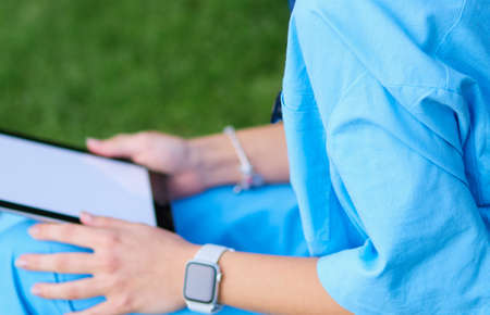 Woman doctor using tablet computer while sitting on grass.Healthcare, insurance and medicine concept Stock fotó