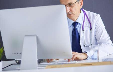 Portrait of senior doctor sitting in medical office Reklamní fotografie