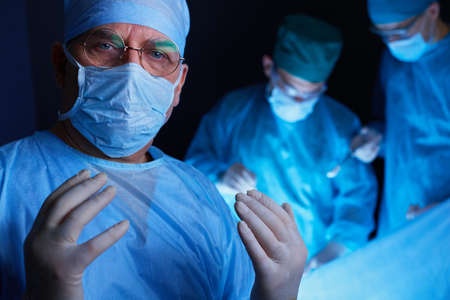 Group of surgeons at work in operating theater toned in blue. Medical team performing operation Stock fotó