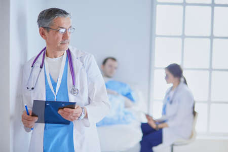 Doctor holding folder in front of a patient and a doctor 免版税图像
