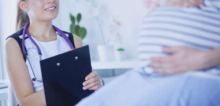 Young woman doctor with stethoscope and tablet speaking with pregnant woman at hospital.