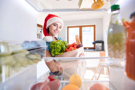 Portrait of female in santa hat standing near open fridge full of healthy food, vegetables and fruits