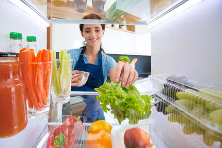Portrait of female standing near open fridge full of healthy food, vegetables and fruits Banco de Imagens
