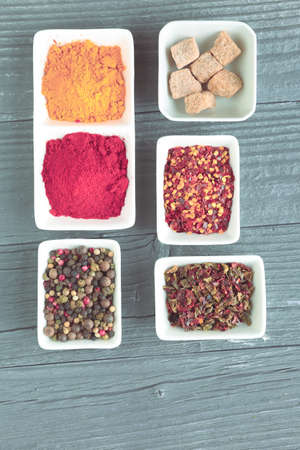 Various spices in a bowls on gray background