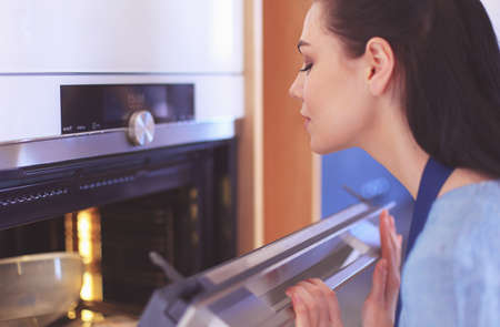 Beautiful young woman checking how her cake is doing in the oven 免版税图像