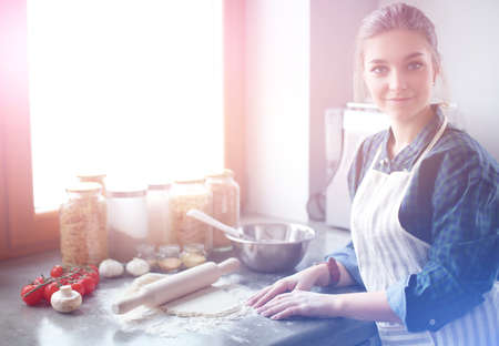 Beautiful woman cooking cake in kitchen standing near desk.