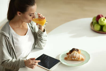 Young woman with orange juice and tablet in kitchen. 免版税图像