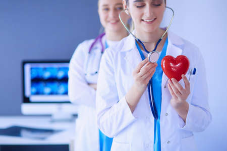 Cropped shoot of two young doctors female with stethoscope holding heart.