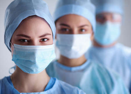 Surgeons team, wearing protective uniforms,caps and masks Zdjęcie Seryjne