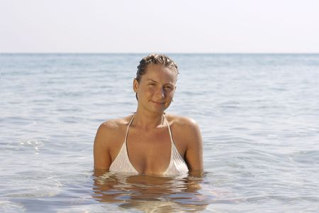 Young woman in the clear and calm sea. photo