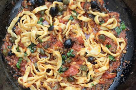 puttanesca: Pan of freshly cooked beautiful fettuccine puttanesca.