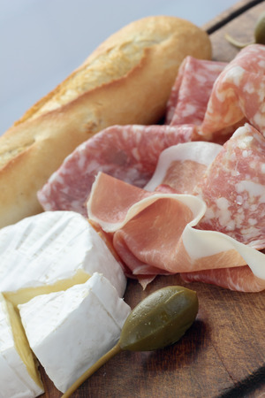 cured ham: Appetizers board with Camembert, cured ham, salami and capers.