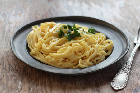 alfredo: Fettuccine alfredo with butter, parmesan and parsley on a tin plate.