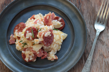 cured ham: Risotto with sausage, cured ham and rosemary on a tin plate.