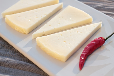 matured: Four slices of semi matured manchego cheese. Stock Photo