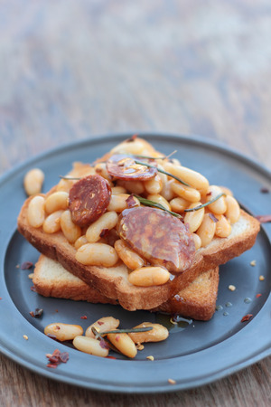 beans on toast: Toast with beans and chorizo cooked with rosemary leaves on a tin plate.