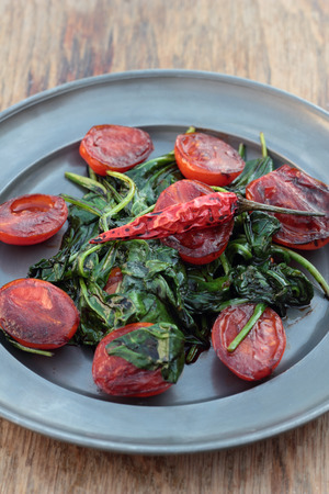 vegetable tin: Fried tomatoes with spinach leaves and chili.