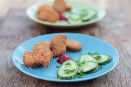 nuggets: Chicken nuggets with sliced cucumber and ketchup.