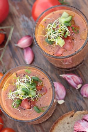 freshly prepared: Two glasses of freshly prepared gazpacho with vegetable topping.