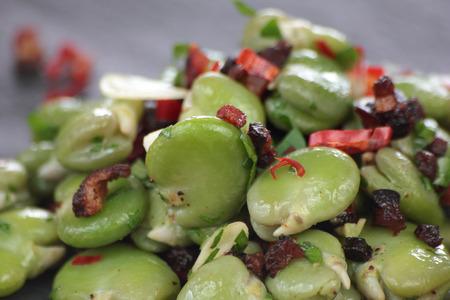 Closeup of broad beans, bacon and chili salad.