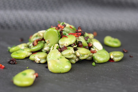 broad: Closeup of broad beans, bacon and chili salad.