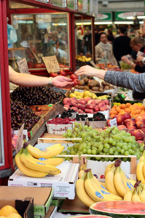 fruit market: The woman pays for vegetables and fruits. Market in Gdynia.