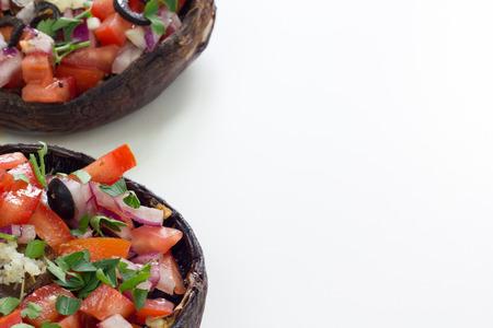 portobello: Grilled portobello mushroom topped with chopped vegetables. Isolated on white.