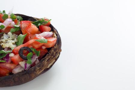 picada: Champiñones portobello a la parrilla cubierto con verduras picadas. Aislado en blanco.