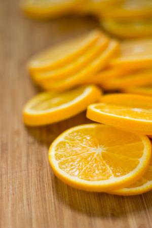orange: Sliced oranges on a timber cutting board.