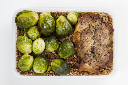 boxed: Fried pork cutlets with  brussels sprouts and buckwheat in a lunch box.