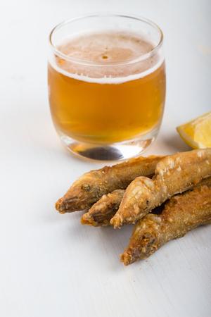 lemon wedge: Fried ladyfish with lemon and glass of beer.