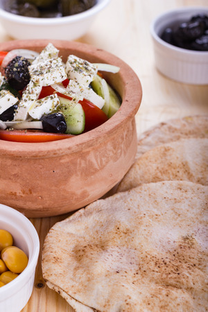 Greek salad with pitas and appetizers on timber table.
