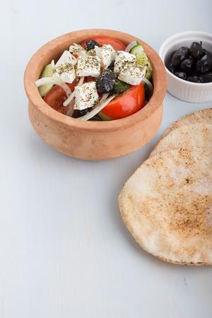 greek pot: Insalata greca in una pentola di terracotta con focacce e antipasti. Archivio Fotografico