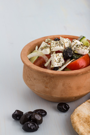 greek pot: Greek salad in a clay pot with pitas and appetizers.