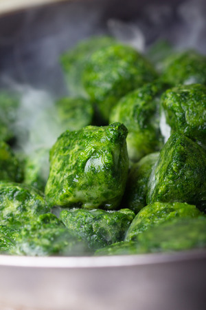 briquettes: Frozen nice and green briquettes of spinach are being cooked on a pan. Stock Photo