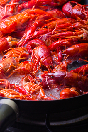 Crayfish are being cooked on a frying pan.
