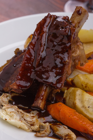 Flat rib with sauted vegetables served on a white plate.