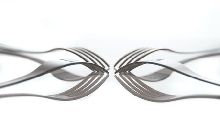 four forks on white reflected in table top