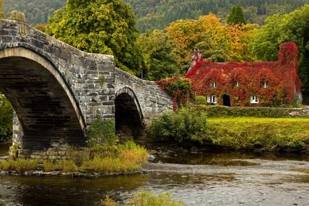 Llanrwst brug en Hof huis bedekt met rode ivy Stockfoto