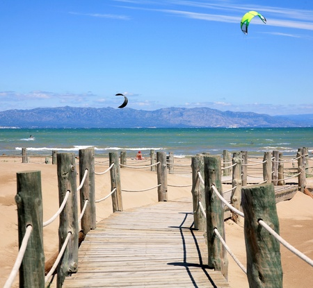 Wooden stairs and kite surfers on the beach Riumar Spain