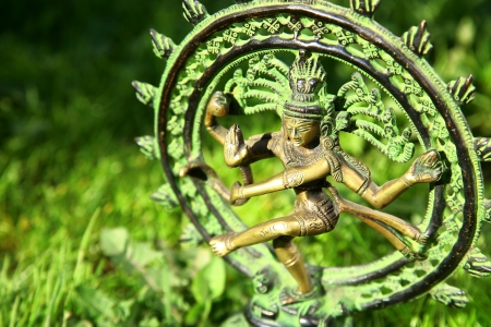 asana: Statue of Shiva - Lord of Dance on green grass background Stock Photo