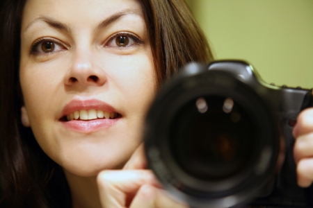Smiling young brunette woman photographer  photo