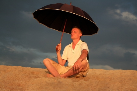 Man with umbrella on the beach on vacation. Sardinia. Italy. photo
