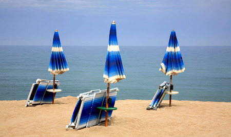 idling: Beach chairs on the sand beach with cloudy blue sky and sun Stock Photo